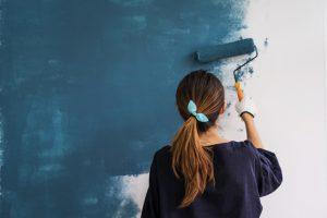 woman painting interior wall