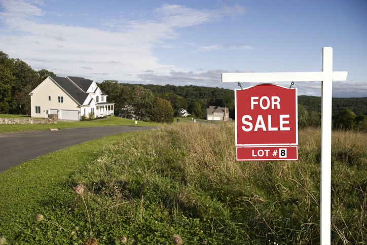 Real Estate sign showing land is for sale in a new subdivision.